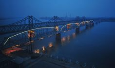 Dusk falls over the Yalu River on April 3, 2009, which seperates the North Korean town of Siniuju (opposite) from the Chinese city of Dandong, as lights are turned on along the Yalu River bridge, also known as the no-name bridge. The full-length bridge built right beside the no-name bridge remains busy during the day time as trucks, trains and other vehicles transport goods back and forth.