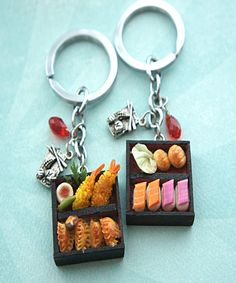This keychain features a miniature bento box adorned with handmade sushi sculpted from polymer clay. The bento box charm measures 2cm x 2cm and is securely attached to a silver tone key chain. The key