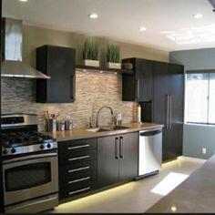 modern kitchen. Dark cabinets, white floor, stainless appliances, getting closer.