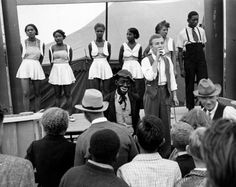 alfred eisenstaedt - life goes to a county fair: 5 gals of the harlem dandys on stage with blackface comic, 1938