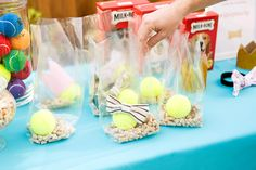 Fill up goodie bags with dog treats, tennis balls + dog accessories to give out at your puppy party. #partner