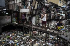 Manila, Philippines  Residents rest on a wooden bridge over a rubbish-filled waterway in Manila. Photograph: Noel Celis/AFP/Getty Images