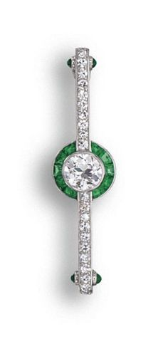 AN ART DECO DIAMOND & EMERALD BAR BROOCH, CARTIER, LONDON,  CA 1925. Centering an old European-cut diamond weighing approx 1.10 cts, encircled by calibré-cut emeralds, flanked by 22 single-cut diamonds, the sides of the terminals accented with 4 cabochon emeralds, mounted in platinum, signed Cartier Ltd., London. With signed case.