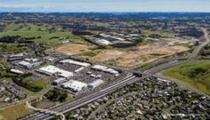 Looking north-west across the top of the North-western Motorway, the original Westgate centre and the earthworks for the new town centre & employment zones, including the Marinovics' strawberry fields, and the suburb of Massey North in the foreground. Oct 2013.