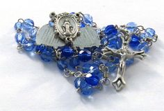 This rosary has a rare center medal which fans out to read the mysteries of the rosary. It does not have the Mysteries of Light, as it was originally created before the addition by Saint Pope John Paul II. *********************************  All of our rosaries are handcrafted with pride of workmanship in our smoke-free facility. We use wire wrapped bows as connectors on all of our rosaries, making for a sturdy rosary that will withstand even the hardiest of prayer warriors. Because of this…