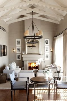you can't help but love the white exposed ceiling beams & industrial chic chandelier in this beautiful living room.