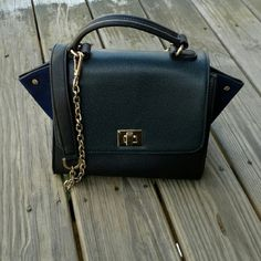 "Pre-loved Izzy & Ali Bag This Lily Mini Trapeze bag in Navy was bought at Southmoon Under. It has a turn lock flap and gussetted sides for extra room. Gold hardware with champagne colored lining. Interior has one zip pocket and two multifunctional pockets. Comes with deattachable shoulder strap. There are no rips, tears or stains on the inside of the bag. It measures 9.5""W x 7.5""H x 4.5""D.  The last picture shows signs of wear on the turn lock and corners of the bag. More pictures can be…"