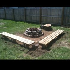 Firepit with custom benches that the bottoms are large stakes that were put in the ground for better stability, also used a large stump for added seating!