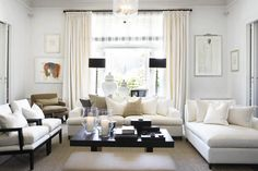 White living room, white sofas with neutral pillows. Love black floor lamps