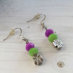 These are super adorable small silver cross earrings for both you and that special little girl in your life.  We all know that little girls love to wear mom's jewelry.  These colorful cross earrings are made with a lime green bead and a magenta bead.    These Christian cross charm earrings measure 1.75 inches (4.445 centimeters)    Every Christian child should have some Christian jewelry and these cross earrings can even be shared with each other.    Christian earrings are so important for…