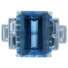 Remarkable Color Natural Aquamarine Diamond Platinum Cluster Ring. Beautifully architectural in design platinum ring prong set in the center with a rare and richly colored natural aquamarine measuring 13.6 mm. x 10.2 mm. weighing approx. 7.0cts. Each side is set with three baguette cut diamonds totaling approx . 75cts. grading VS clarity G color. Size 3 1/2 and can be sized. Circa 1950.