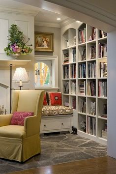 library in corner of living room with small bench under window and recessed lighting