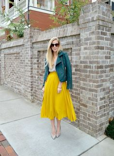 pleated mustard yellow skirt and green leather jacket