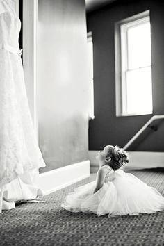 Flower girl looking at wedding dress. So cute!!