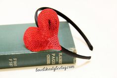 This is a beautiful red color sequined heart headband on the black satin headband. ($13)