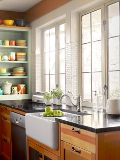 An apron-front sink, a gooseneck faucet, and soapstone counters lend vintage charm, while micro-sized ceramic subway tile adds a modern kick to this open-plan kitchen.