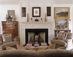 The living room fireplace was marbleized by English decorative painter Dawn Reader. Neoclassical obelisks and urns on the mantel mix with English antiques. Club chairs upholstered in linen velvet and a copious olive beige sofa — all fabrics and furniture from Nicholas Haslam — give the room a cozy sophistication. - HouseBeautiful.com