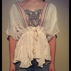 """Meghan Fabulous Cloud Forrest Top This top is brand new. It does not have tags as it was shipped this way. It was only taken out of package to model and take photos. It is white with multicolored embroidery. It has an open v back. It is 100% rayon. It is very flowy and loose. It has a string that can be tightened or loosened. It is approximately 20"""" across the bust when laid flat and 26 1/2"""" long. This top is a small, but can definitely fit, and may better fit a medium as well. Meghan Los…"""