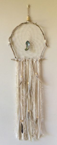 Beautiful custom made Driftwood Dreamcatcher, pictured here in neutral colours. Add one of these mystical pieces to any room & drift away to a peaceful sleep or day dream.  These vary on size (depending of size of wood available). The one pictured is a medium size which is roughly around 26 cm diameter. They are made from natural drift wood, feathers, neutral coloured ribbon & a piece of paua shell.  Every dreamcatcher is slightly different because they are made to order and eacused is…