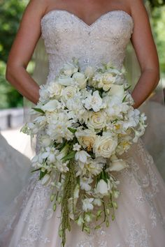 Cascade bouquet with white orchids, white peonies, cream roses, white stephanotis, white tulips, white mini callas, gardenia, and hanging amaranthus.