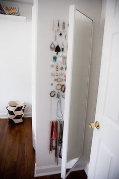 Utilize the space behind a full-length mirror to store jewlery.