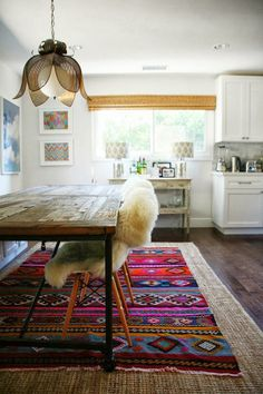 Jute and aztec pattern layerd rugs... love the wall art in the back, the chandelier and the sheepskin!