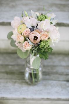 The bride carried a romantic spring bouquet of ranunculus, sweet peas, Juliet garden roses, viburnum, lavender, sweet peas, herbs, silver dollar eucalyptus, dusty miller, spray roses, and silver brunia.     Photo by Kate Preftakes Photography