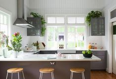 The IKEA kitchen fits perfectly among the light-filled space at the rear of the home. The kitchen makes the most of the high ceilings, with plants above the cupboards. The stools are from Kmart. Kitchen Plants, Ikea Kitchen, Kitchen Items, Home Decor Kitchen, Kitchen Cabinets, Cupboards, Kitchen Photos, Kitchen Cleaning, Wall Cabinets