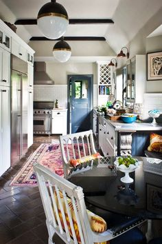 Love this kitchen. Persian rug, moody blue accents, wood accents, white cabinets. everything LEB: mind games