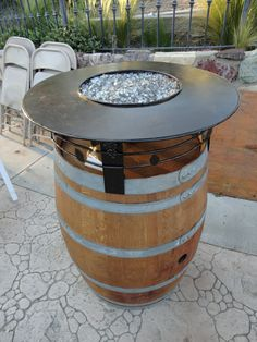 Here is a Wine Barrel Fire Pit designed and built by Leasure Concepts. The top is fabricated out of steel with iron deco grapes and leaves. The entire assembly is high heat powder coated bronze. The fire pit features a stainless steel fire ring with Fire Crystals bronze and clear glass. The bottom half of the barrel is saw cut for a propane tank and the gas key is located in the cork hole of the wine barrel. This rustic looking fire pit is a great touch to any wine enthusiasts home or outdoor li