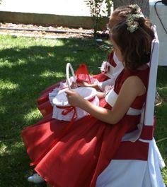 Lucía y Emma fueron junto con los novios las grandes protagonistas. Vestidas con un precioso vestido rojo con lazo blanco, zapatos blancos y florecitas naturales en blanco y rojo para adornarles el pelo. Emma fue la encargada de abrir el cortejo lanzando pétalos blancos y rojos que llevaba en una cestita a juego y cubriendo toda la alfombra con ellos. En Lucía confiamos para que llevara las alianzas en un original bastidor, también en blanco y rojo.