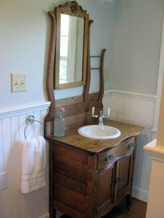 Antique oak hotel commode re-purposed into a bathroom vanity, just had to raise the mirror to an appropriate eye level...still hope they used a water proof finish.