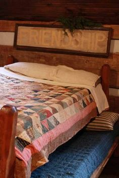 ...old trundle bed w/ quilt..love the sign above bed...