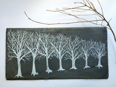 Original art hand-painted on a vintage roof slate shingle. Minimal art painting of a lane of bare trees, this black and white painting of winter trees is fresh and fashionable art for your home. Painted on a vintage slate shingle harvested from a 100+ year-old roof in Baltimore, Maryland. The white paint is textured and manipulated to look like a chalk drawing on slate, but is durable and fade-proof. The vintage slate has chips, bevels and two worn nail holes, which are artifacts from being…