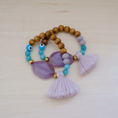 These bracelet feature a purple agate, purple tassel attached, agate beads, and wooden beads Handling time 1-2 business days