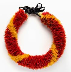 Lei hulu (feather lei), 19th century. Yellow 'ō'ō (Moho sp.) feathers, red Kuhl's lorikeet (Vini kuhlii) feathers, and black ribbon. Bernice Pauahi Bishop Museum, Ethnology Collection