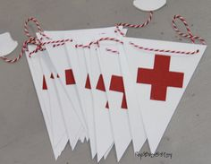 Red Cross - Nursing - Healthcare - Party Banner Simple, yet makes the perfect statement! The perfect banner for your graduation or retirement party! This banner is 7 feet long with 20 pennants. Each pennant is made from cardstock and has a red cross adhered to the front. Each pennant is 3.5