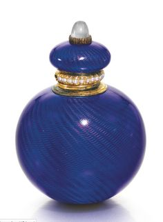A Fabergé gold-mounted enamel scent bottle, workmaster Henrik Wigström, St Petersburg, 1903-1904. Spherical, the surface of translucent royal blue enamel over wavy engine-turning, the cushion-form lid set with a moonstone, the rim mount with seed pearls, struck with workmaster's initials, 56 standard, numbered.