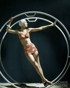 Exercise Ring and Jantzen Swimsuit  A 1940s-era exercise ring becomes an unusual prop in this John Rawlings photograph. A model wears a red-and-white printed Jantzen swimsuit, composed of a skirt and bra top. Her pose is quite sculptural, and placed inside the ring, she becomes part of a well-conceived still life. The image appeared in the June 1946 Glamour.