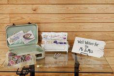 Guests leave well wishes for the bride & groom. Love the small mint green suitcase, vintage white sewing drawer, and vintage floral handkerchief
