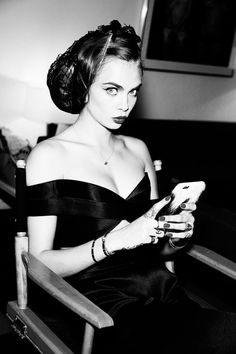 Captured in black and white, Cara Delevingne takes a moment to glance away from her cell phone for Sunday Times Style Magazine February 2016 issue