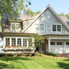The broad gabled roof anchors the surrounding dormers and is an eye-catching focal point of this new construction home. #lakehouse #gabledroof #architecturaldesign #waterfront #lakelife #newconstruction #cottage #cottagestyle #charm #flowerboxes #endlesssummer