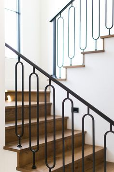 A wooden staircase is accented with wrought iron ornate spindles and a wrought i. - A wooden staircase is accented with wrought iron ornate spindles and a wrought iron handrail. Staircase Spindles, Iron Handrails, Wood Handrail, Wrought Iron Stair Railing, Stair Railing Design, Metal Railings, Iron Spindle Staircase, Bannister, Stair Treads