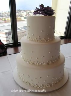 "Wedding cake delivered to the Space Needle, Seattle, December 30th, 2011. Handmade sugar peony topper, and cascading ""champagne bubbles"" piped with Royal Icing."