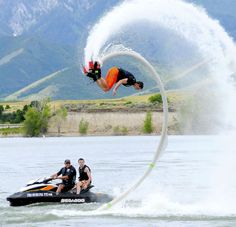 Weston Curtis does tricks in the air while riding a Fly Board as Roger Smith and Spencer Sorensen watch at Hyrum Reservoir. The board mounts to your feet and water pressure goes through a hose that splits into two nozzles beneath your feet creating lift. (Photo by Eli Lucero)