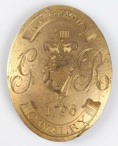 "1796: RATHDOWN CAVALRY OFFICER'S SHOULDER BELT PLATE    An oval George III Officer's shoulder belt plate engraved with crowned Maid of Erin harp.   Surrounded and surmounted by Royal Cypher and above the date 1796"". Scrolls above and below containing the name of the regiment.   Reverse with double stud and single hook."