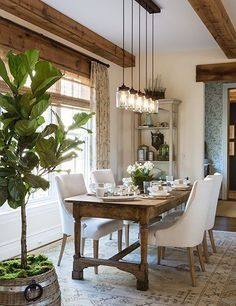 Dining Room decor ideas - Rust Farmhouse style with natural wood table and beams and upholstered white chairs.