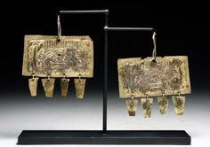 Northern Peru, Ca 200 to 500 CE.  A large pair of matching ear decorations, of hand-hammered gold sheet with impressed image of Ai Apec with toothy grin and series of four trapezoidal dangles at the bottom of each earring.