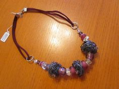 The necklace is small clear/pink/purple round glass beads with 3 large silver wired circles in between them at the front and are on a plain red cord.   eBay!