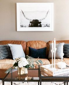 Brown sofa that matches ours. Greyish beige walls, navy and neutral pillows and glass/ iron table